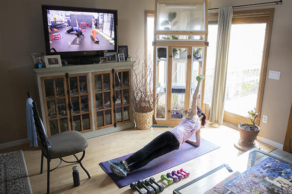 Rhonda Branca, director of Lyceum, works out at home to a virtual exercise class offered by a local gym during the New York state COVID-19 pause.