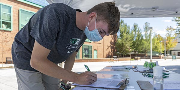 Incoming student Daniel Lounebery of Syracuse registers to vote at the Center for Civic Engagement table during Move-in Week Aug. 20, on the Spine, outside the entrance near the Bookstore.