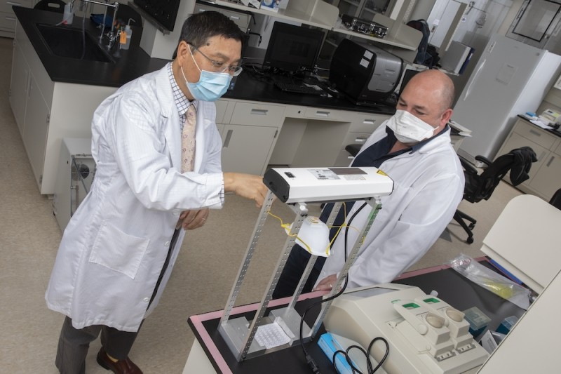 Biomedical engineers Kaiming Ye, department chair, and Guy German, Associate Professor/Graduate Program Director, developed a system that uses ultraviolet light to sterilize personal protective equipment in the early days of the pandemic. It was quickly deployed by local hospitals. Now the team has turned its attention to the use of UV light to disinfect large, enclosed spaces and to determining the amount of UV light necessary for sterilization and the amount that's safe for human health. Photo taken at Ye's lab in the Biotechnology Building of the Innovative Technologies Complex.