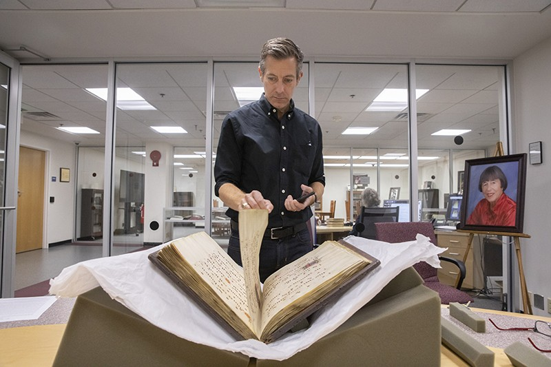 Paul Schleuse, associate professor of musicology, examines Binghamton University's newest manuscript -- the Gradual of La Crocetta.
