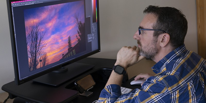 Jonathan Cohen edits one of the thousands of photos he has taken for the University.
