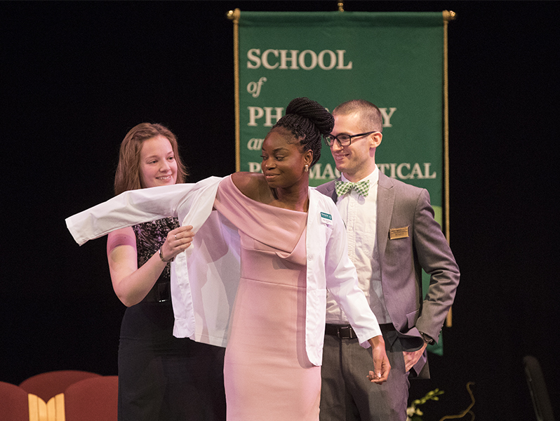 Mavis Adu-Bonsu was the first student to receive a white lab coat from faculty Erin Pauling and William Eggleston during the inaugural School of Pharmacy and Pharmaceutical Sciences White Coat Ceremony held at the Watters Theater on Sept. 9.