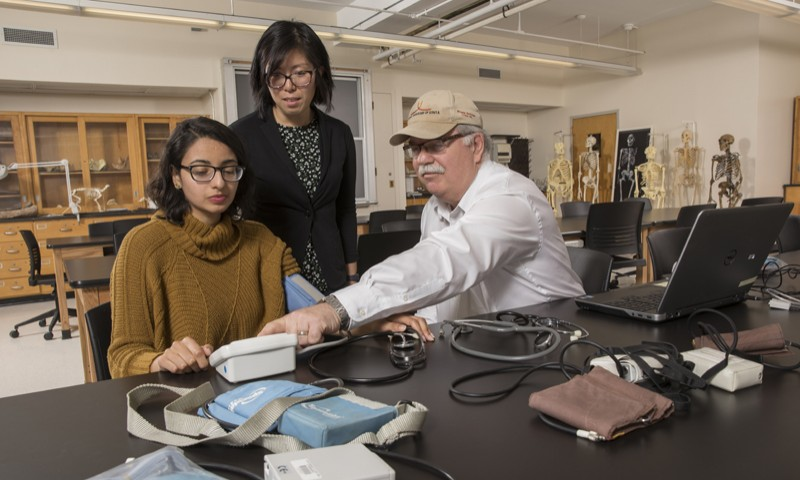Gary James, graduate director of the biomedical anthropology program, works with students Zara Shah, left, and Jane Pechera in Science 1.