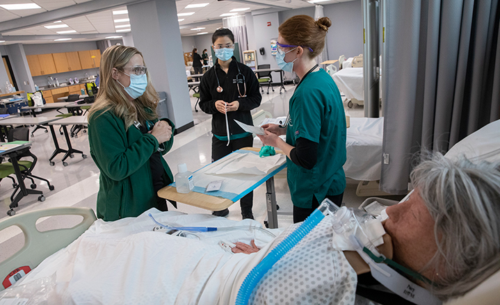 Decker College Baccalaureate Accelerated Track nursing students Hikari Ochi (center) and Catherine Kanwisher (right) were among the first students to use the new Innovative Simulation and Practice Center at Binghamton University's Health Sciences Building in Johnson City. They are pictured with instructor Amy Perrin, FNP.