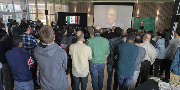 Distinguished Professor M. Stanley Whittingham speaks by video conference to a crowd gathered at the Smart Energy Building about his Nobel Prize in Chemistry. Whittingham was at a scientific meeting in Germany when the prize was announced.