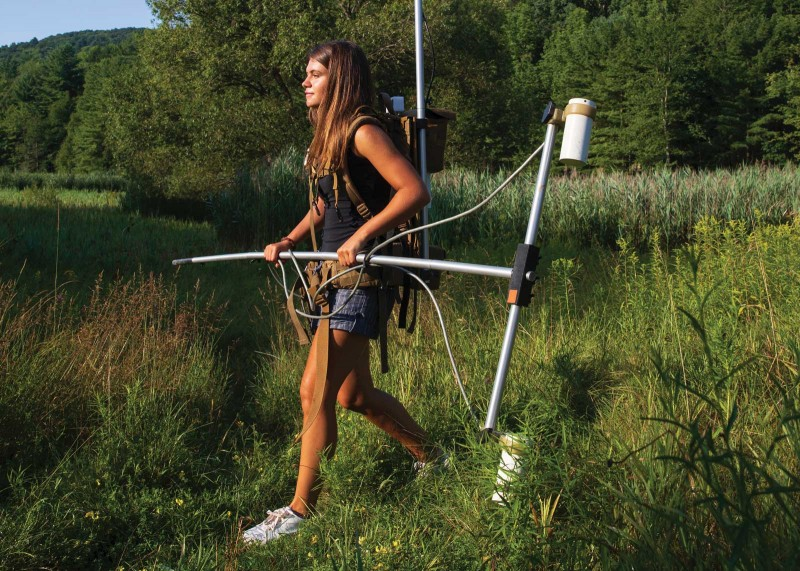 Natalia Romanzo, a master's student in sustainable communities, is wearing about 40 pounds of equipment, including a magnetometer and a battery pack. The equipment is still being used, but drones are increasingly providing a more practical alternative.