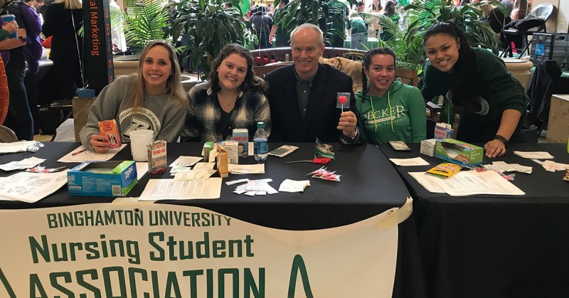 Binghamton University President Harvey Stenger stopped by the Nursing Student Association's table during the University's Day at the Mall event in February 2019. He was welcomed by NSA members (from left) Kate Annesi, Emily Guida, Gabrielle Cornelious and Alyssa Vilda.