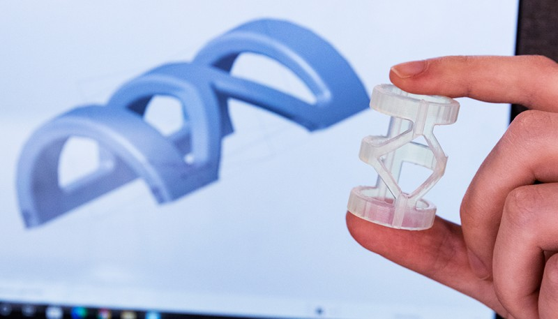 The blue image is a computer-aided design (CAD) model of the orthosis the students developed for people with injuries to the proximal interphalangeal joint (PIPj) of the fourth digit of the hand. In the foreground is a 3D-printed model of the device.
