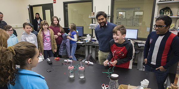 Graduate students Nahid Hasan, left, and Nabid Hossain demonstrate how they convert mechanical vibrations into electrical energy during a field trip for children from Tioga Hills Elementary School in late April.