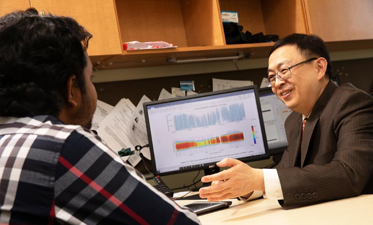 Ning Zhou, an associate professor of electrical and computer engineering, meets with graduate student Tawsif Ahmad.