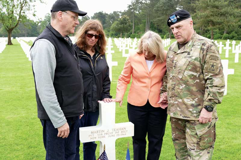 Jim and Monica Farrell and Holly and Gen. Mark Milley at Martin Teahan's gravestone in the Normandy American Cemetery.