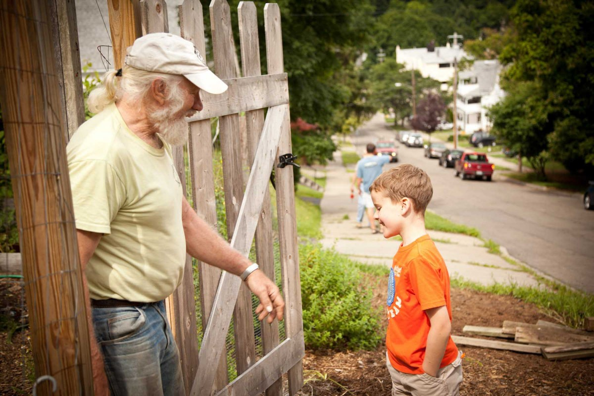 Professor Dick Andrus greets a neighborhood youth at a VINES community garden in Binghamton.