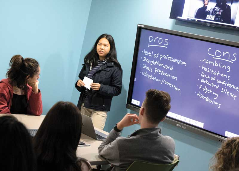 Sophomore Trinh Nguyen, an undergraduate peer mentor, coaches students on interviewing skills.