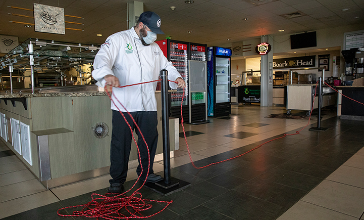 Thomas Dello, executive chef at Binghamton University Dining Services, installs rope and floor decals at the Appalachian Collegiate Center at Mountainview College.