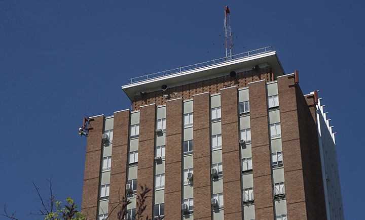 A worker connecting cell phone antennae atop the Glenn G. Bartle Library Tower.