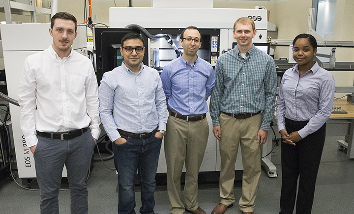 Assistant Professor Scott Schiffres (center) with students working in his lab in front of the 3D metal printer used for this research.