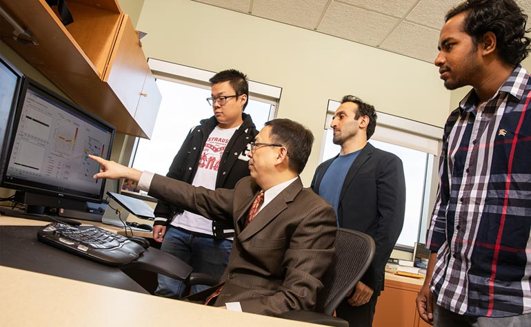 Ning Zhou, an associate professor of electrical and computer engineering, explains a concept about power grids to, from left, graduate students Yuting Chen, Hossein Sangrody and Tawsif Ahmad.